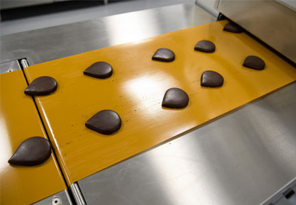 At AAK's new innovation center at Edison, N.J., droplet-shaped shortbread cookies, made in the bakery lab, received a chocolate coating in the confectionery lab during the open house