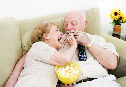 Baby Boomers couple snacking on popcorn