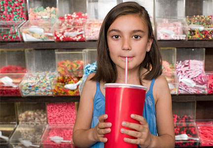 Child drinking soda in a candy store
