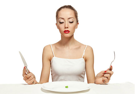 Woman on diet with not much to eat on her plate
