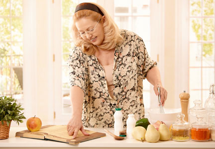 Baby Boomer woman cooking with a recipe