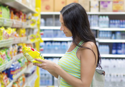 Woman reading chip label in grocery store aisle