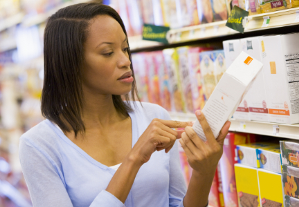 Woman reading label of snack packaging