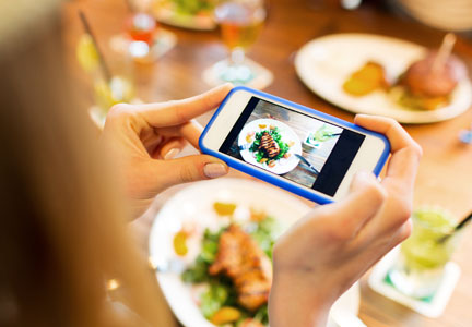 Woman taking picture of food at restaurant with cell phone, social media